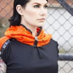 """Shirt: Black ribbed polyester, short top. Collar and sleeves in orange, stretch jersey fabric with akiaki print in yellow, red and black. Lacquer detail in front of both sleeve  Tights: see """"BOTTOMS""""."""